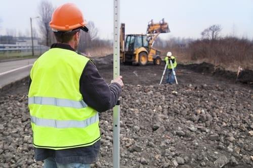 Arpenteurs au travail avec le creuseur comme arrière-plan.